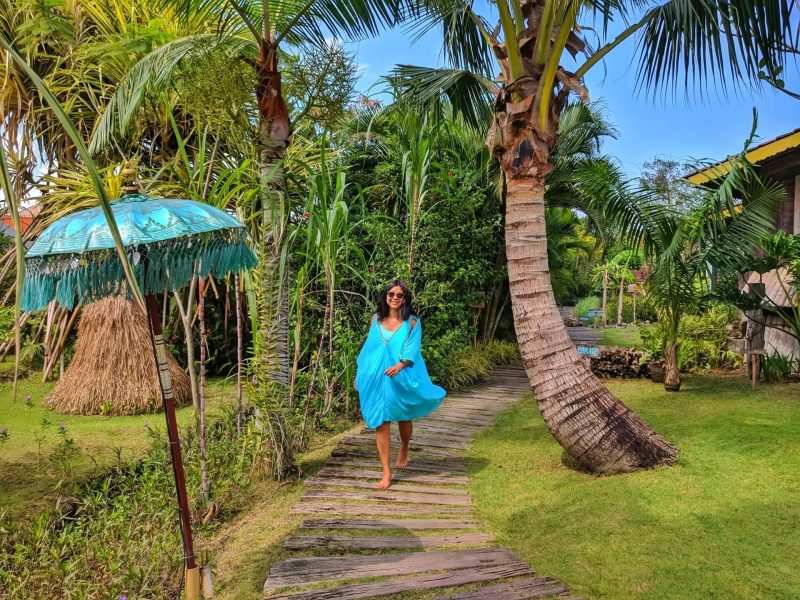 In Bali, walking down path in jungle background with palm trees and umbrella